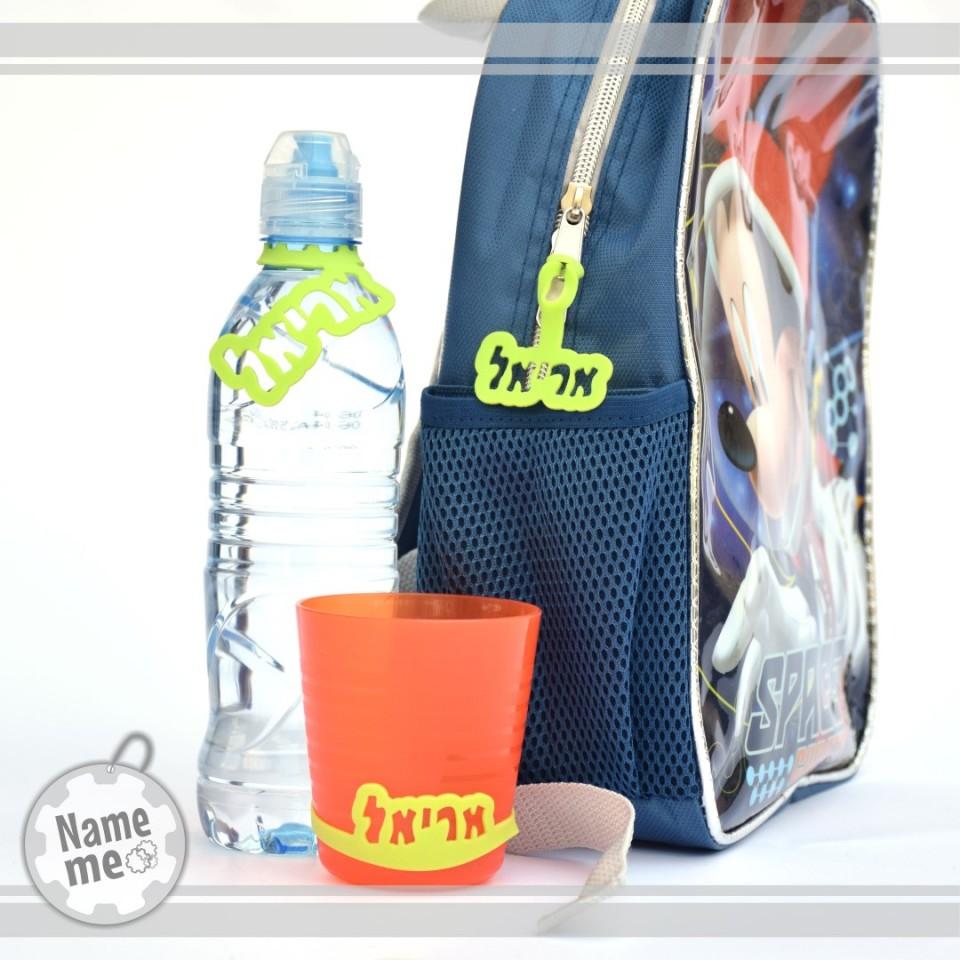 בתמונה תווית שם על תיק, על כוס ועל בקבוק מים.